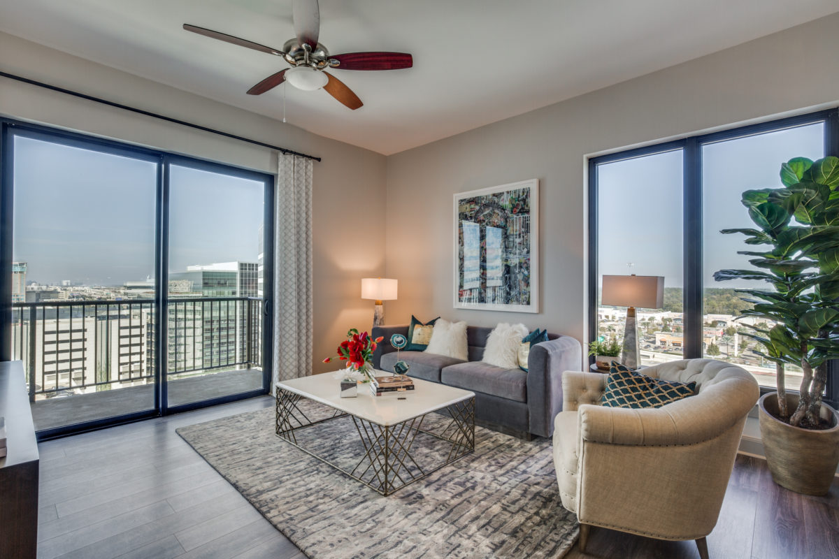 Living room with wrap around city views at The McCarthy Apartments in Memorial City Houston